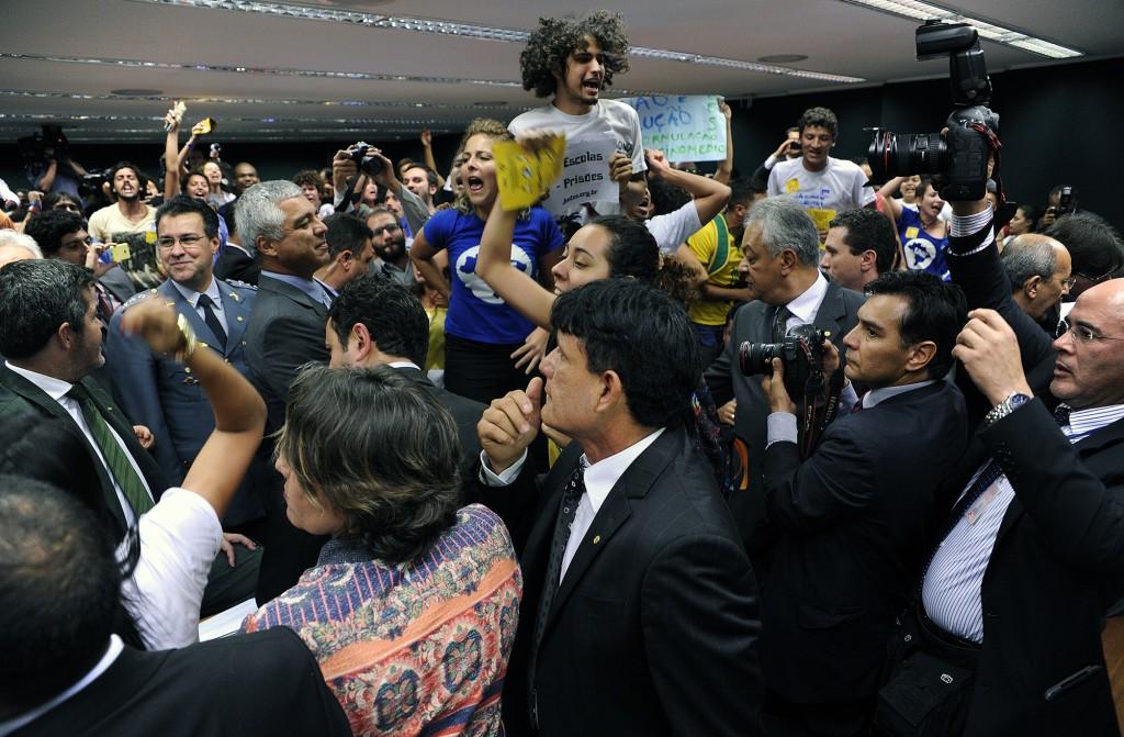 Deputado Capitão Augusto (PR-SP, fardado) sorri diante de manifestação contrária à redução da maioridade penal. Em seguida, ele disse que os manifestantes teriam cometido crime. (Foto: Lucio Bernardo Jr./Câmara dos Deputados)